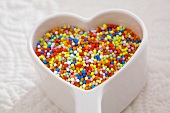 Hundreds and thousands in heart-shaped dish