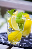 Mineral water with lemon wedges and mint leaves