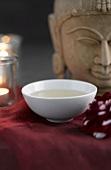 Green tea in tea bowl, Buddha head in background