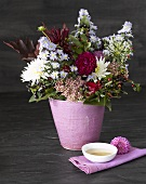 Flowers in pink pot and bowl of tea