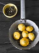 Yellow baby patty pan squashes in pan, pumpkin seeds in bowl