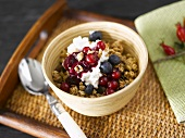 Muesli with yoghurt & berries in wooden bowl on wooden tray