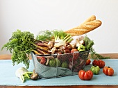 Organic vegetables and baguettes in wire basket