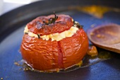 Tomato stuffed with sheep's cheese in a frying pan