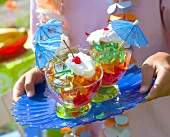 Coloured jelly cubes with cream, cocktail cherries, umbrellas