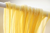 Home-made ribbon pasta hanging over kitchen spoon (close-up)