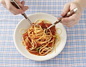 Eating spaghetti and tomato sauce with spoon and fork