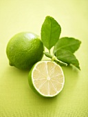 Whole lime and half a lime with leaves