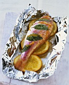 Red mullet with orange slices on aluminium foil