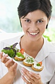 Woman holding a tray of open sandwiches