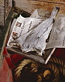 Stockfish on newspaper in an old boat (California)