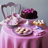 Chocolate cake, macarons and cupcakes on small table