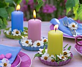 Candles with zinnias in small quiche dishes