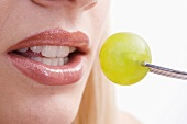 Young woman eating a grape