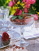 Dried rose petals and fresh rose in a glass
