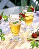 Eistee mit Erdbeerminze und frischen Erdbeeren an Glas