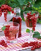 Redcurrant syrup in bottles & diluted with water in glasses