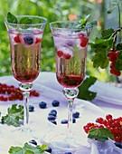 Getränke mit Johannisbeersirup und Eiswürfel mit Beeren