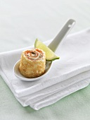 Pancake roll filled with smoked salmon on porcelain spoon