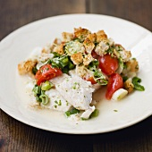 Baked fish fillet with croutons and spring onions