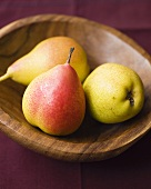 Three pears in a wooden bowl