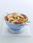 Cooked coloured spiral pasta in a metal colander