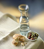 Pickled olives, pieces of baguette and a carafe of water