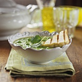 Pea soup with mint leaves and toast