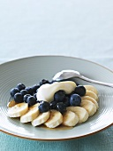 Banana and blueberry dessert with honey and cream