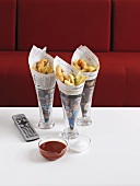 Fish and chips in newspaper and remote control