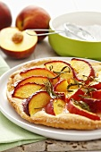 Sweet pizza topped with peach slices and rosemary