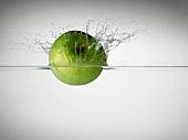 Grüner Apfel, ins Wasser fallend