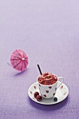 Berry ice cream in a cup, cocktail umbrella