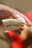 Child's hand holding a sandwich