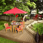 Laid table with red sun shade on decking