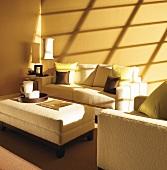 Wohnzimmer mit Sofa, Sessel, Hocker & Schattenspiel an der Wand