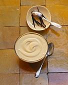 Vanilla cream with vanilla pods on tiled surface