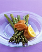 Green asparagus with smoked salmon on glass plate
