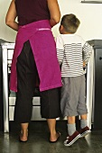 Mother and son standing at stove in kitchen