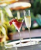 Fruity redcurrant drink and a glass of sparkling wine