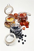 Blueberries, peaches and strawberries in preserving jars