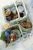 Fruit salad, dried fruit and biscuits in picnic baskets