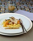 Poached zander on vegetables with hazelnut vinaigrette