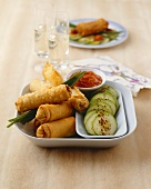 Meat-filled spring rolls with cucumber and spicy sauce
