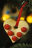 Heart-shaped biscuit with red chocolate beans to hang on the tree