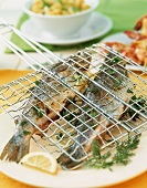 Grilled trout with herbs in a fish basket