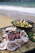 Fresh calamari in a towel and a pan on the beach