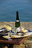 Champagne, olives and bread with fresh cream on a table by the sea