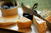 Various types of soft cheese on a cheese board with a cheese knife