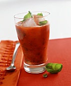 A tomato and basil drink over ice
